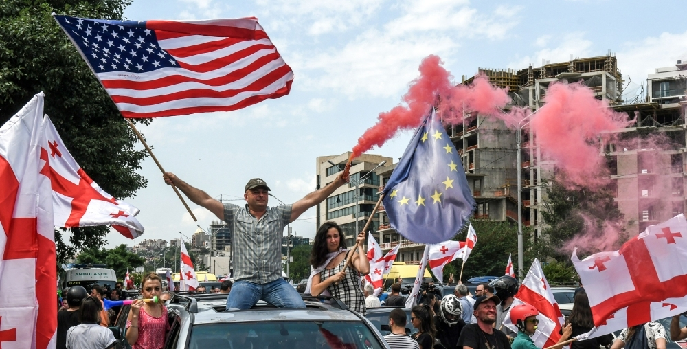 Protesters waive the EU, Georgian, right, and American flags during a motorcade rally in Tbilisi, Georgia, on Monday. — AFP