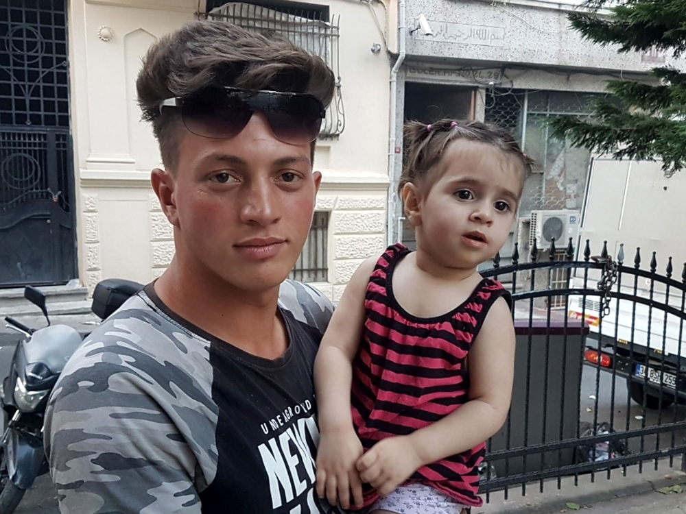 Algerian citizen Feuzi Zabaat, left, 17, poses with Syrian toddler Doha Muhammed he caught as she was falling from the second floor at Fatih district in Istanbul on Thursday. — AFP