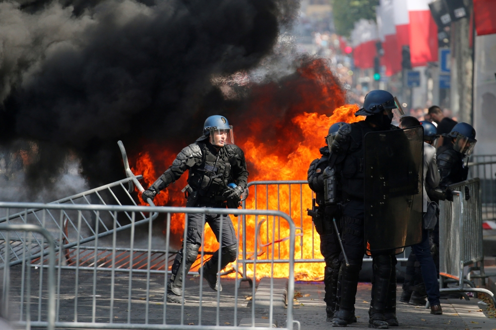 French Gendarmes remove fences next to a burning portable toilet during clashes with protesters on the Champs Elysees avenue after the traditional Bastille Day military parade in Paris, France, on Sunday. — Reuters