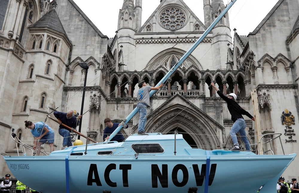 Extinction Rebellion climate activists raise a mast on their boat during a protest outside the Royal Courts of Justice in London on Monday. -Reuters photo