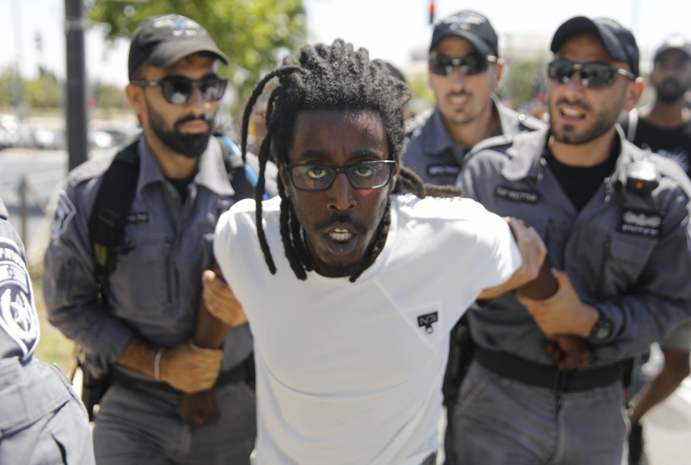 Policemen detain an Israeli man of Ethiopian origin during a protest outside the Knesset (Israeli parliament) in Jerusalem on Monday following the death of a young man of Ethiopian origin who was killed by an off-duty police officer in Kiryat Haim near the Israeli city of Haifa on June 30.  — AFP
