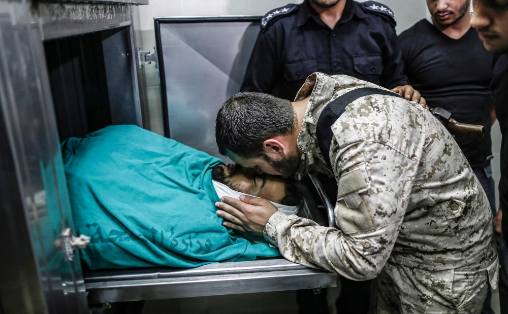 A member of Hamas' security forces mourns over the body of 28-year-old Hamas fighter Mahmoud Al-Adham, at a hospital morgue in Beit Lahya in the northern Gaza Strip, in this July 11, 2019 file photo. — AFP