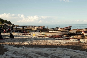 Malawian fishermen fix their fishing nets as fishing boats are seen on the shore of the Lake Malawi at the Senga village on May 19, 2019 in Senga, Malawi.  -AFP photo