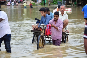 An Indian rickshaw driver transports commuters on a flooded street after a heavy downpour at Baldakhal village in Agartala, the capital of northeastern state of Tripura, on Sunday. -AFP photo