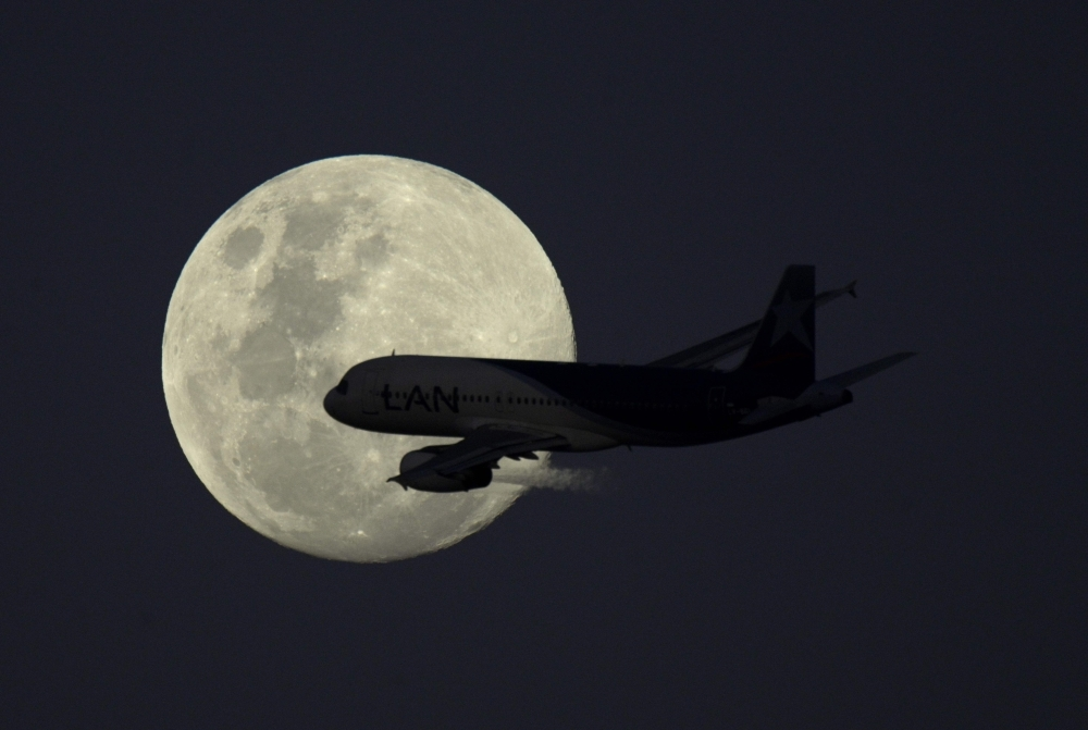 An airplane of LATAM Airlines flies in front of the moon after taking-off from Jorge Newbery airport in Buenos Aires, Argentina, on Monday. — AFP
