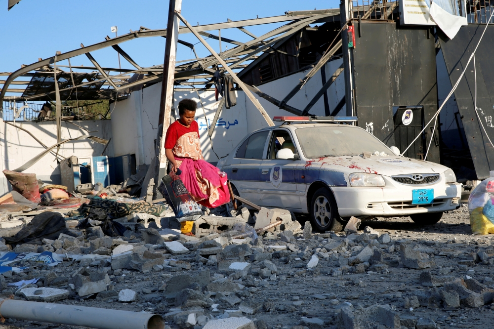 A migrant picks up clothes from among rubble at a detention center for mainly African migrants that was hit by an air strike in the Tajoura suburb of the Libyan capital of Tripoli in this July 3, 2019 file photo. — Reuters