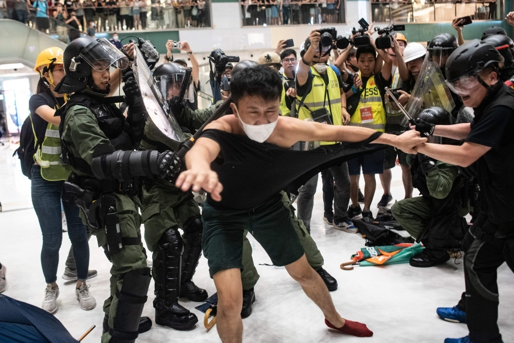 Police officers tear the shirt of a protester during a clash inside a shopping arcade after a rally against a controversial extradition law proposal in Sha Tin district of Hong Kong on July 14. -AFP photo