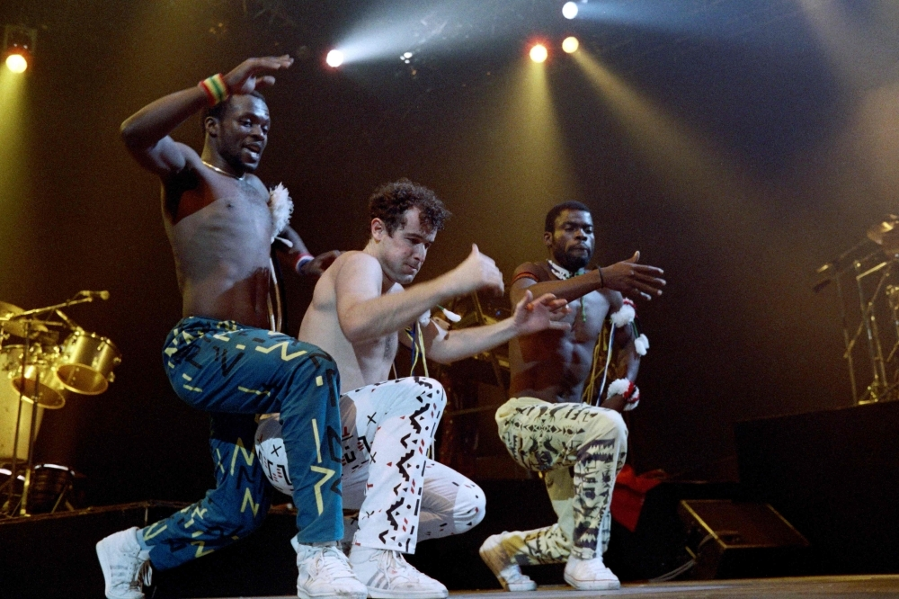 In this file photo taken on May 10, 1988 South African singer Johnny Clegg (C) and dancers of South African band Savuka perform on stage at the Zenith concert hall in Paris as part of three-concert series dedicated to the fight against apartheid. — AFP