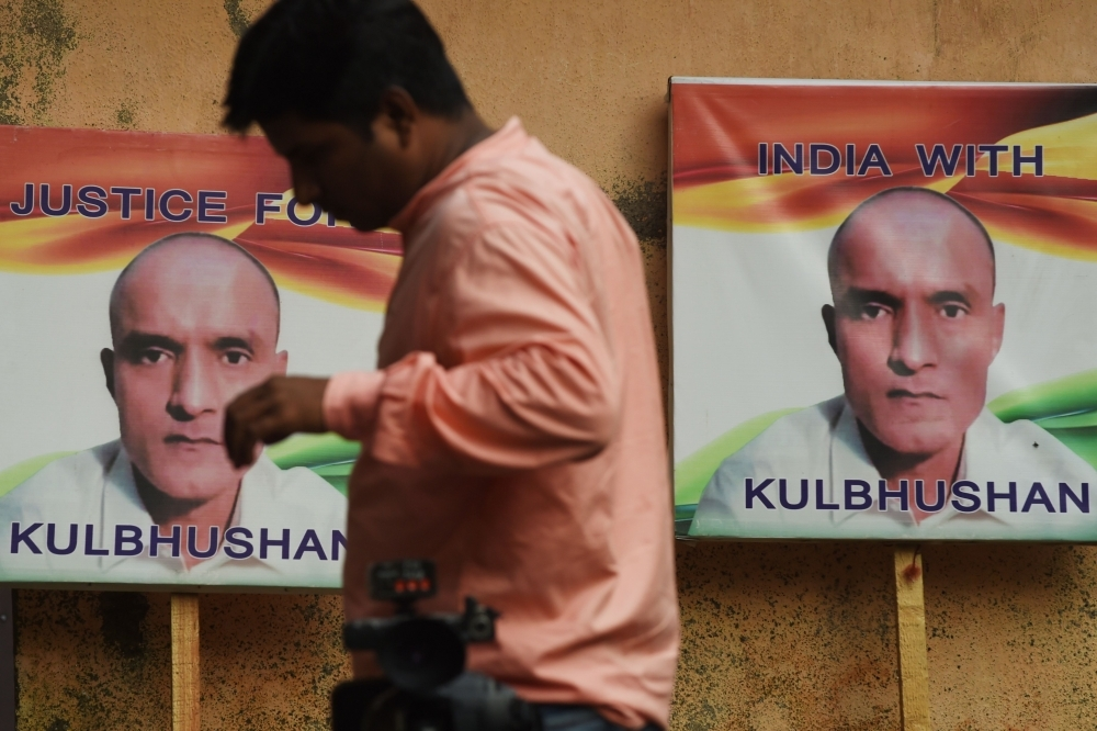 An Indian resident walks past placards with the picture of Kulbhushan Jadhav, an Indian national convicted of spying in Pakistan, in the neighborhood where he grew up, in Mumbai on Wednesday. — AFP