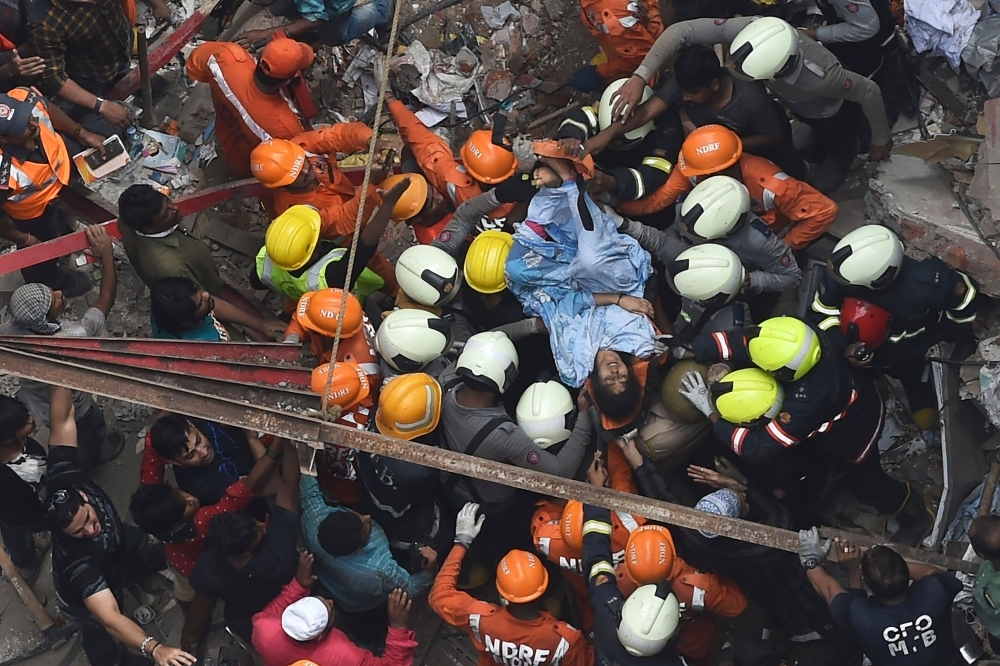 Indian National Disaster Response Force and Indian fire brigade personnel rescue a survivor from after a building collapsed in Mumbai on Tuesday. — AFP