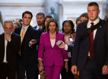 US speaker of the House, Nancy Pelosi walks with reporters, before the Democrat controlled House of Representatives passed a resolution condemning US President Donald Trump for his