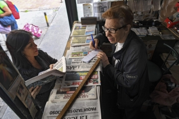 In this photo taken on July 03, 2019, a woman buys printed newspapers at a kiosk in Caracas, Venezuela. Due to the shortage of paper and scarce personnel, the Venezuelan press was pushed to the internet as a way to survive in a country with precarious connectivity. -AFP