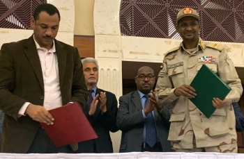 Sudanese deputy chief of the ruling military council Mohamed Hamdan Dagalo (R) and protest movement Alliance for Freedom and Changes leader Ahmad Al-Rabiah stand after inking an agreement before African Union and Ethiopian mediators in Khartoum early on Wednesdau. -AFP photo