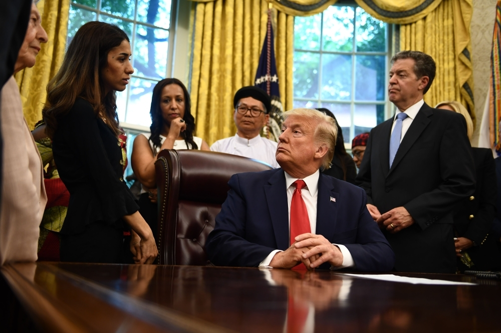 US President Donald Trump meets with survivors of religious persecution in the Oval Office of the White House in Washington on Wednesday. — AFP