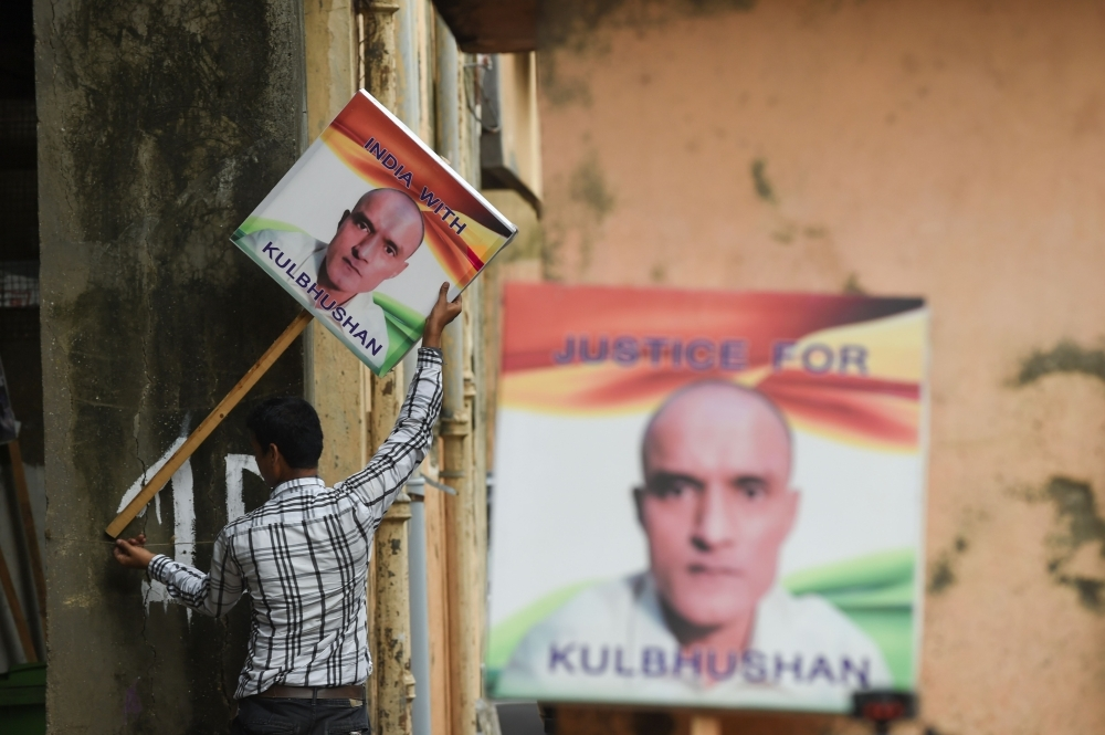 An Indian man holds a placard depicting Kulbhushan Jadhav, an Indian national convicted of spying in Pakistan, in the neighborhood where he grew up, in Mumbai, on Wednesday. — AFP