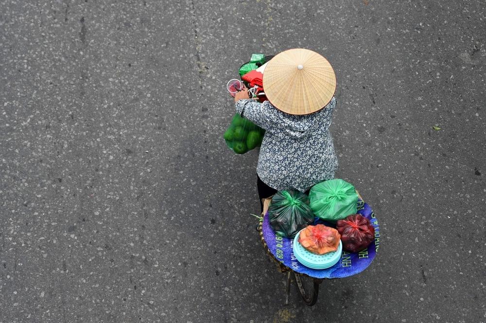 A fruit vendor cycles in Hanoi, Vietnam, on Thursday. — AFP