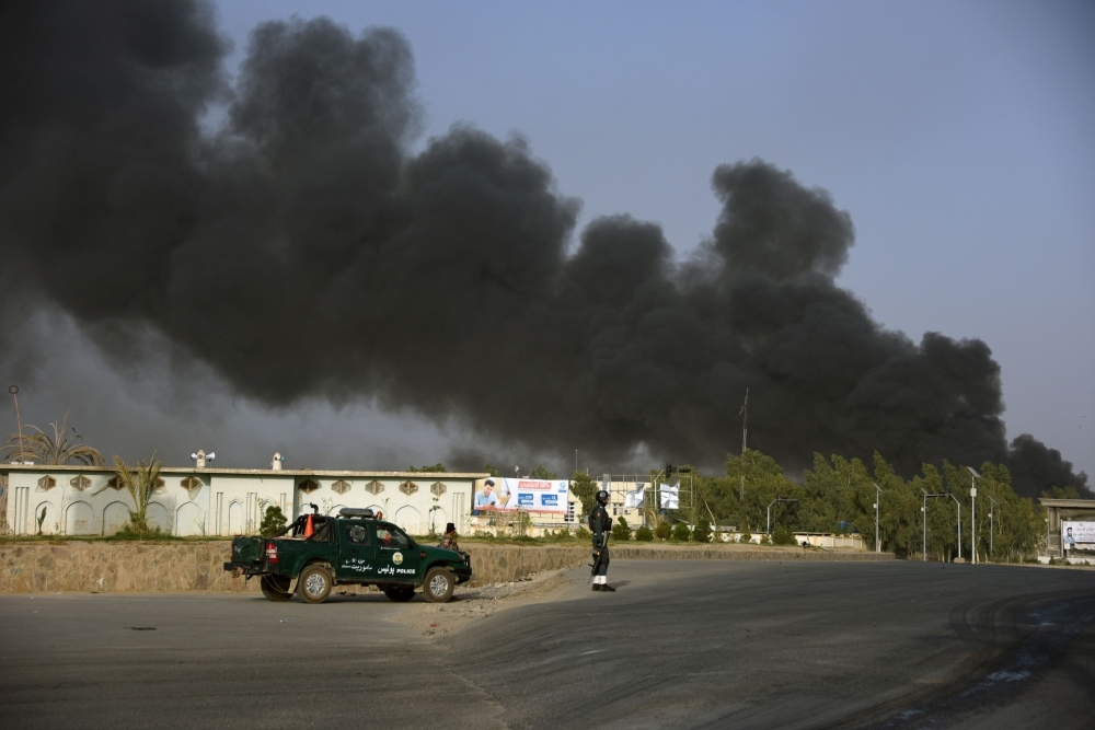 Afghan policemen arrive near a site of car bomb attack as smoke rises from the police headquarters in Kandahar province on Thursday. — AFP