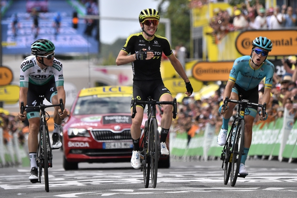 Great Britain's Simon Yates (C), flanked by Austria's Gregor Muhlberger (L) and Spain's Peio Bilbao, celebrates as he wins on the finish line of the twelfth stage of the 106th edition of the Tour de France cycling race between Toulouse and Bagneres-de-Bigorre, in Bagneres-de-Bigorre on Thursday. —  AFP