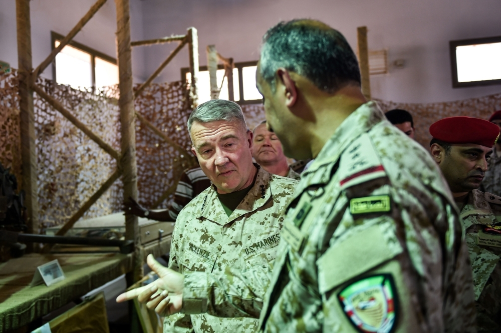 US Marine Corps General Kenneth F. McKenzie Jr. (C, behind), commander of the US Central Command (CENTCOM) and Lieutenant General Fahd bin Turki bin Abdulaziz al-Saud (front), commander of the Saudi-led coalition forces in Yemen, are shown reportedly Iranian weapons seized by Saudi forces from Yemen's Huthi rebels, during his visit to a military base in al-Kharj in central Saudi Arabia on July 18, 2019.  / AFP / Fayez Nureldine
