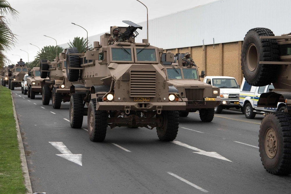 A convoy of South African National Defense Force (SANDF) drives through a street close to Manenberg in Cape Town on Thursday. — AFP