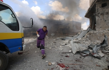 A Syrian rescuer from the Violet NGO runs during airstrikes by Syrian regime forces in Maar Shurin on the outskirts of Maaret Al-Numan in northwest Syria in this July 16, 2019 file photo. — AFP