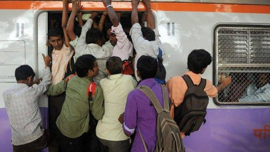 Passengers squeeze into an overcrowded train compartment in Mumbai in this file photo. — AFP