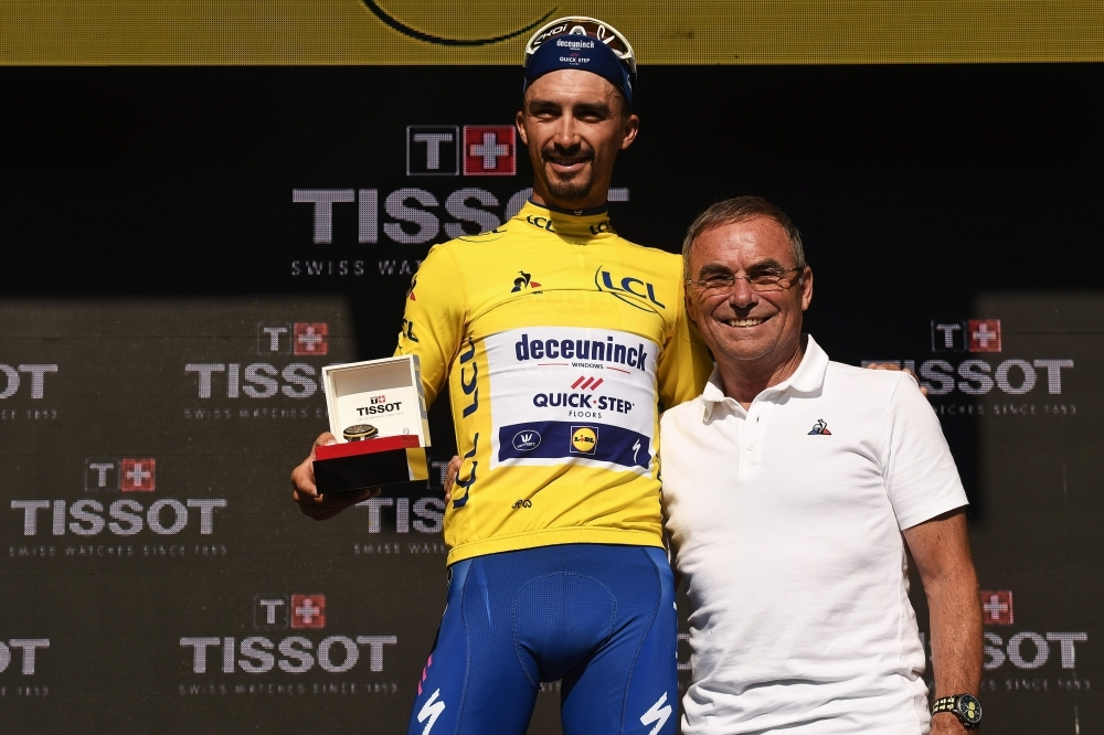 France's Julian Alaphilippe (L) poses with former French champion Bernard Hinault as he celebrates his overall leader's yellow jersey on the podium of the thirteenth stage of the 106th edition of the Tour de France cycling race, a 27,2-kilometer individual time-trial in Pau, on Friday. — AFP