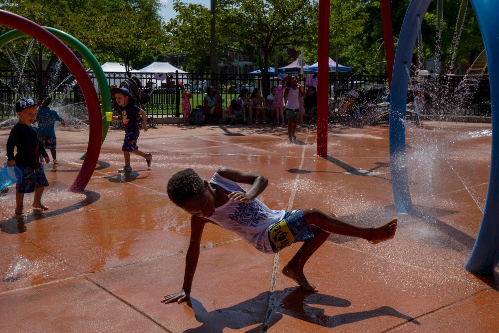 Children cool down at the Petworth Spray Park in Washington on Friday. — AFP