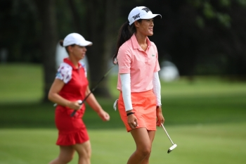 Teammates Karine Icher (L) and Celine Boutier of France walk off the 17th green during round two of the Dow Great Lakes Bay Invitational at Midland Country Club on Thursday in Midland, Michigan.   — AFP