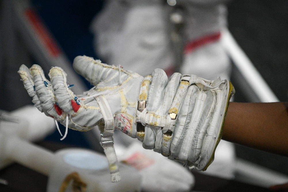 A visitor tries on an astronauts glove during the Apollo 11, 50th Live celebration at Space Center Houston on Friday, in Houston, Texas. — AFP