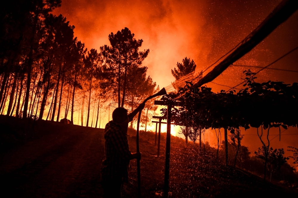 A villager holds a hose as a wildfire comes close to his house at Amendoa in Macao, central Portugal on Sunday. -AFP photo