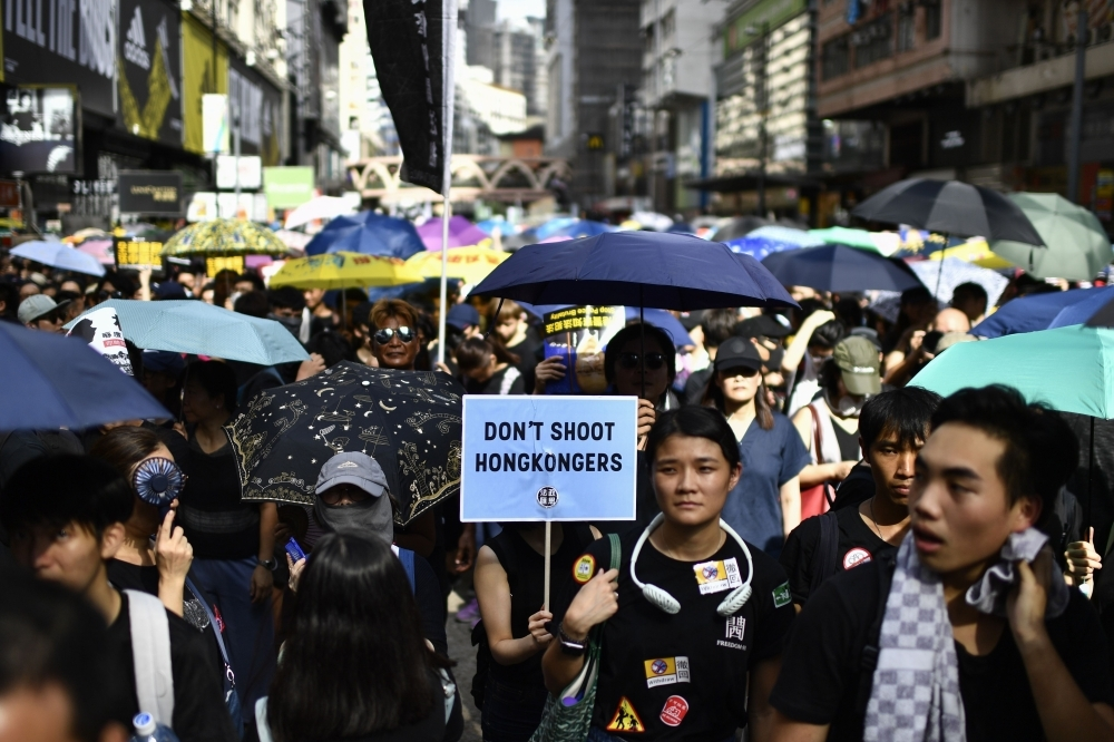 Protesters march against a controversial extradition bill in Hong Kong on Sunday. -AFP photo