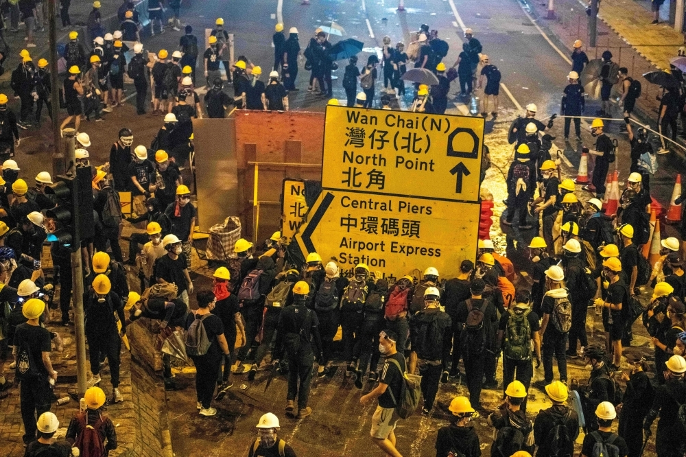 Protesters push a road sign after a march against a controversial extradition bill in Hong Kong on Sunday. Hong Kong descended into chaos on Sunday night as riot police fired multiple volleys of tear at anti-government protesters, hours after China's office in the city was daubed with eggs and graffiti in a vivid rebuke to Beijing's rule. — AFP