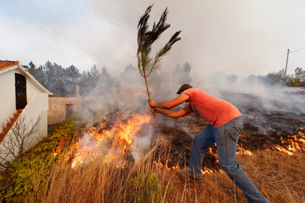 Villagers help to put out a forest fire at the small village of Colos, Portugal on Sunday. -Reuters photo