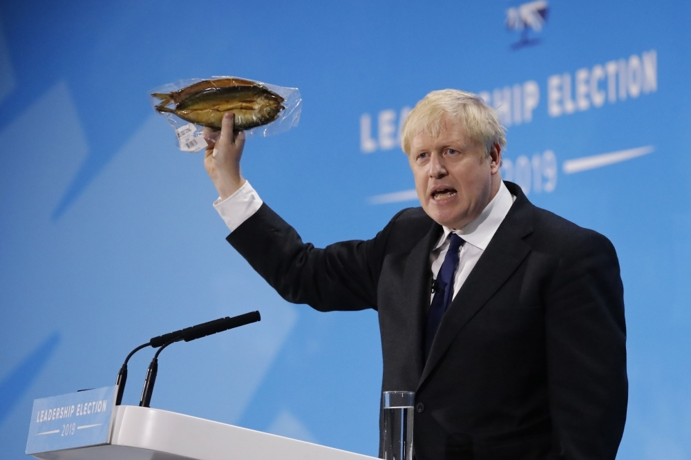 Conservative MP and leadership contender Boris Johnson holds up kipper fish in plastic packaging as he speaks at the final Conservative Party leadership election hustings in London, on July 17. -AFP photo