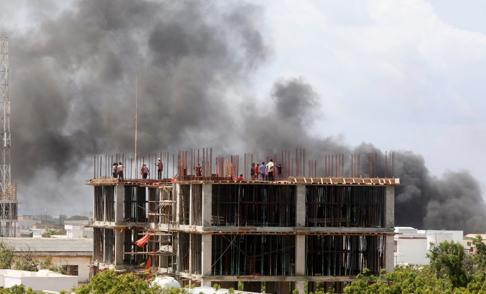 Workers are seen on a construction site as smoke billows from the scene of an explosion in Mogadishu, on Monday. -Reuters photo