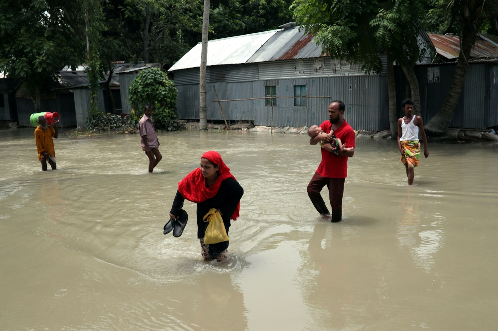 People cross a flooded road in Jamalpur, Bangladesh, on Monday. — Reuters