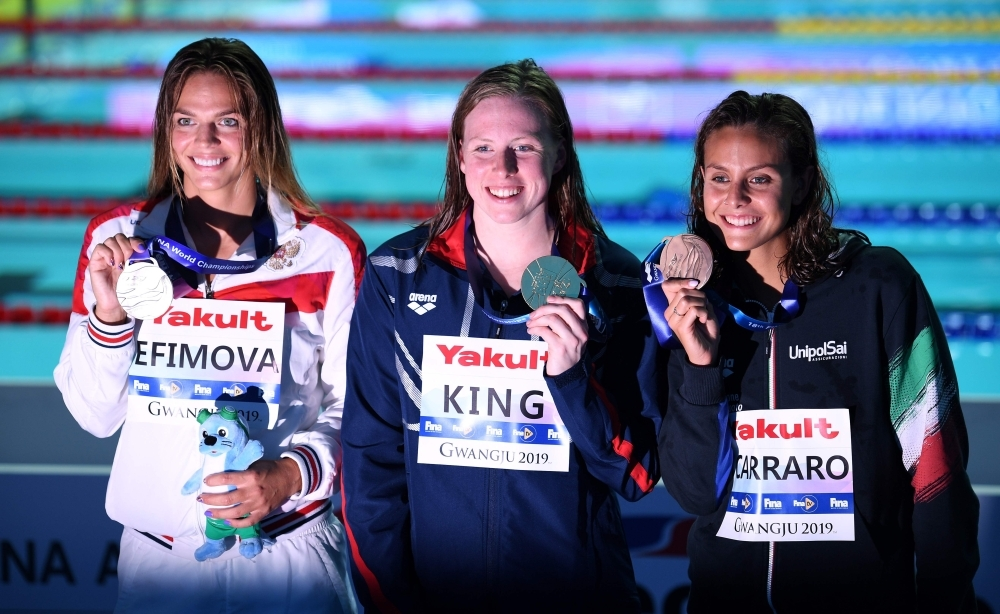 Gold medalist  USA's Lilly King (C), silver medalist Russia's Yuliya Efimova (L) and bronze medalist Italy's Martina Carraro (R) pose during the medals ceremony after the final of the women's 100m breaststroke event during the swimming competition at the 2019 World Championships at Nambu University Municipal Aquatics Center in Gwangju, South Korea, on Tuesday. — AFP