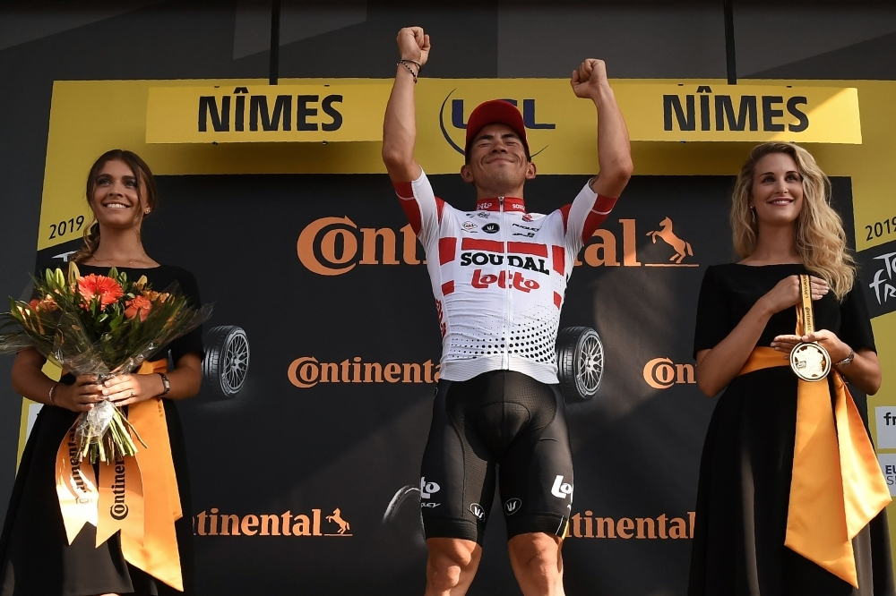 Stage winner Australia's Caleb Ewan (C) celebrates his victory on the podium of the sixteenth stage of the 106th edition of the Tour de France cycling race between Nimes and Nimes, in Nimes, on Tuesday. — AFP