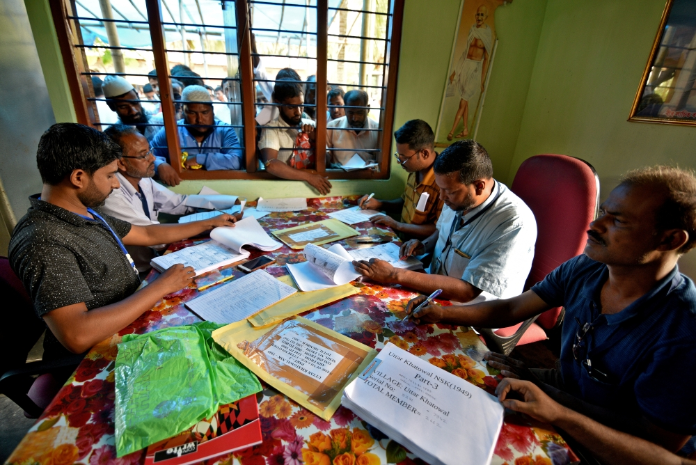 People wait to check their names on the draft list at the National Register of Citizens (NRC) center at a village in Nagaon district, Assam state, India, in this July 30, 2018 file photo. — Reuters
