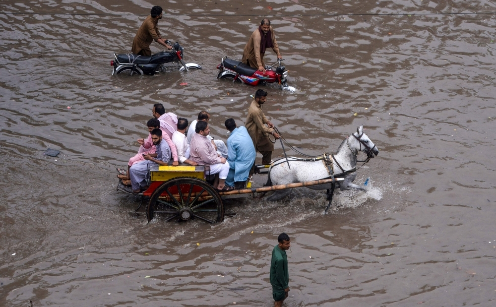 Pakistani residents ride on a horse cart through a flooded street during heavy monsoon rains in Lahore on Thursday. — AFP