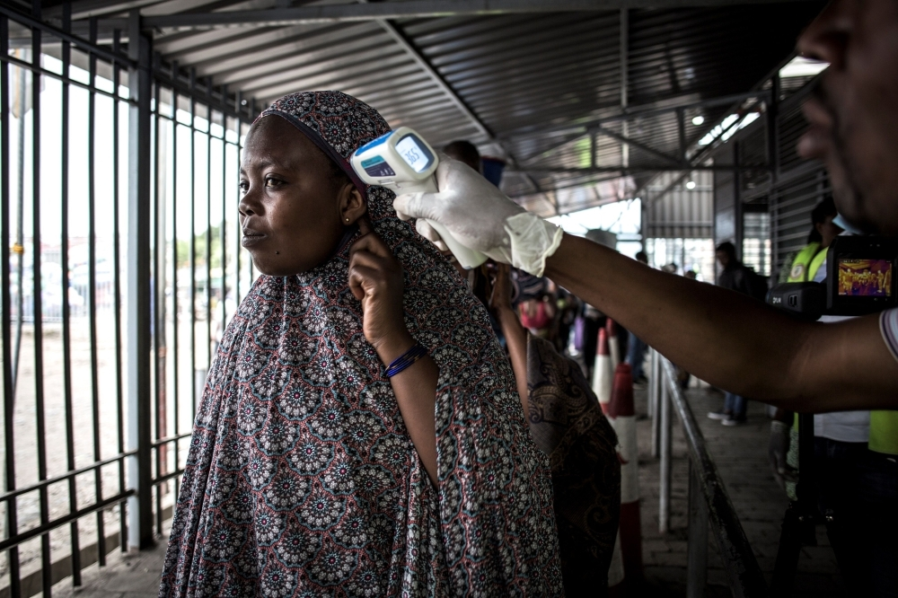 In this file photo taken on July 16, 2019 a woman gets her temperature measured at an Ebola screening station as she enters the Democratic Republic of the Congo from Rwanda  in Goma. -AFP photo