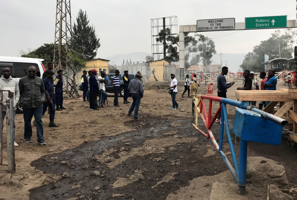 Congolese customs agents gather at the gate barriers at the border crossing point with Rwanda following its closure over Ebola threat in Goma, eastern Democratic Republic of Congo, on Thursday. — Reuters