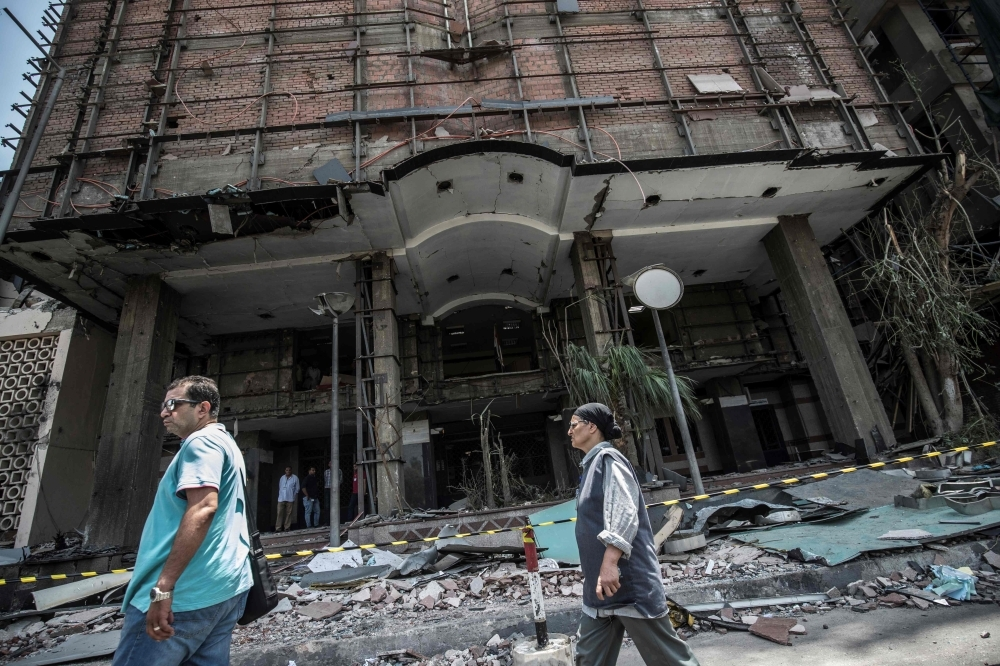 Egyptians walk outside the National Cancer Institute in the capital Cairo on Aug. 5, 2019, where an accident took place just before midnight the previous day. — AFP