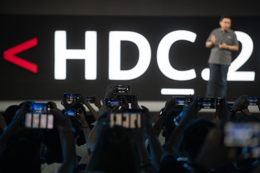 Journalists take pictures as Richard Yu, head of Huawei's consumer business, unveils the company's new HarmonyOS operating system during a press conference in Dongguan, Guangdong province, on Friday. — AFP