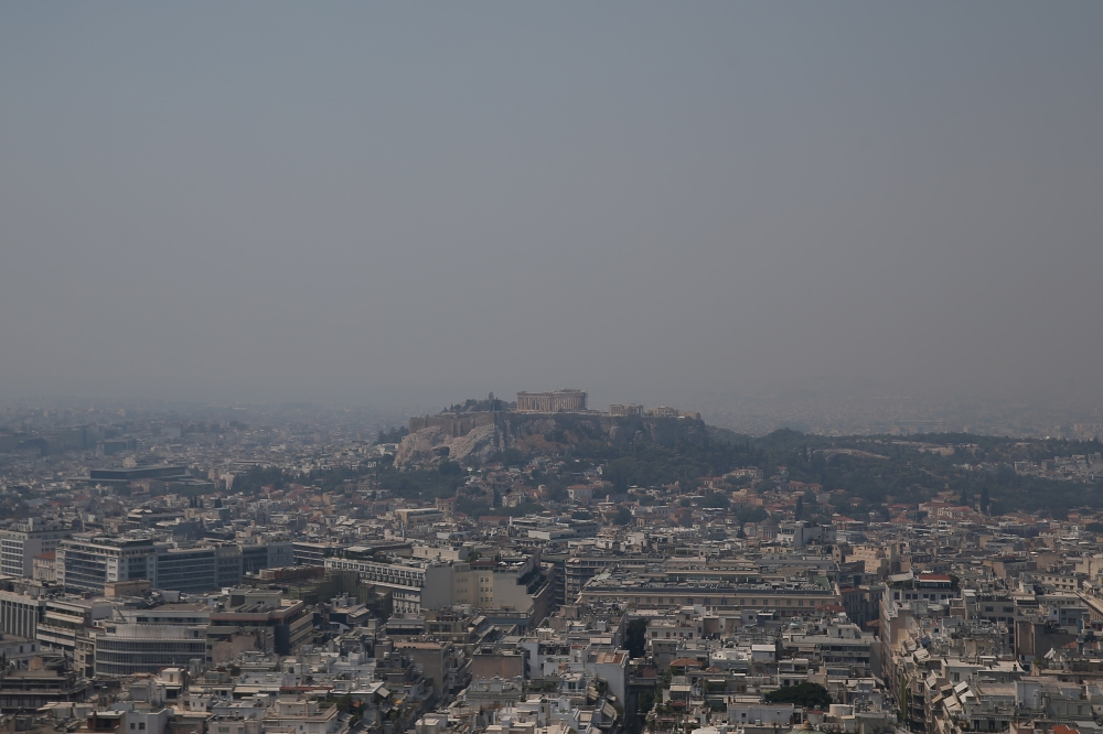 The Acropolis hill with the Parthenon temple is covered with smoke from a wildfire burning the Island of Evia, in Athens, Greece, on Tuesday. — Reuters
