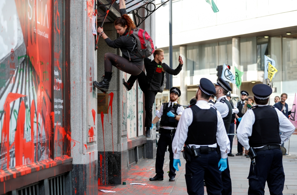 Police officers observe as activists climb down from the awning over the Brazilian Embassy's entrance during Extinction Rebellion climate change protest in London on Tuesday. — Reuters