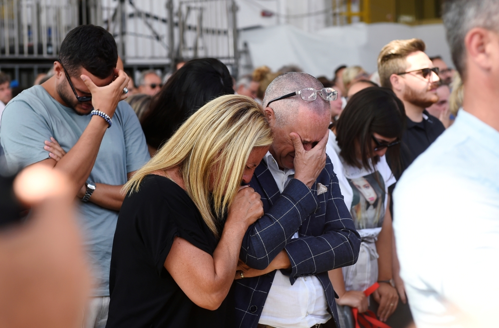 People react as they attend the ceremony marking the first anniversary of the collapse of a motorway Morandi Bridge that killed 43 people in Genoa, Italy, on Wednesday. — Reuters