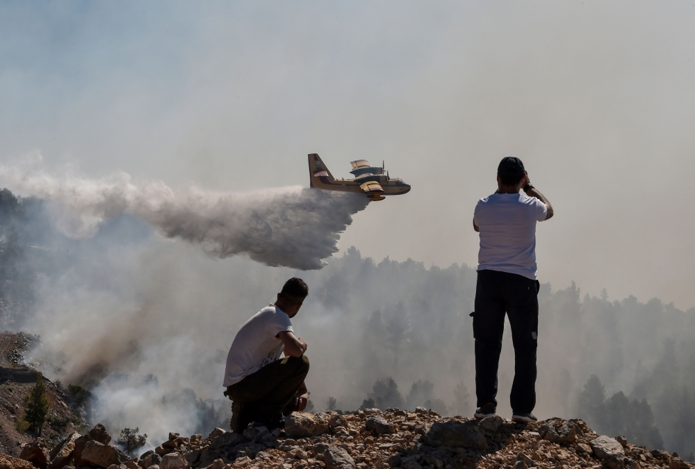 Locals watch a fire-fighting plane dropping water over a wildfire near the village of Stavros, on the Greek Evian island, on Wednesday. — AFP