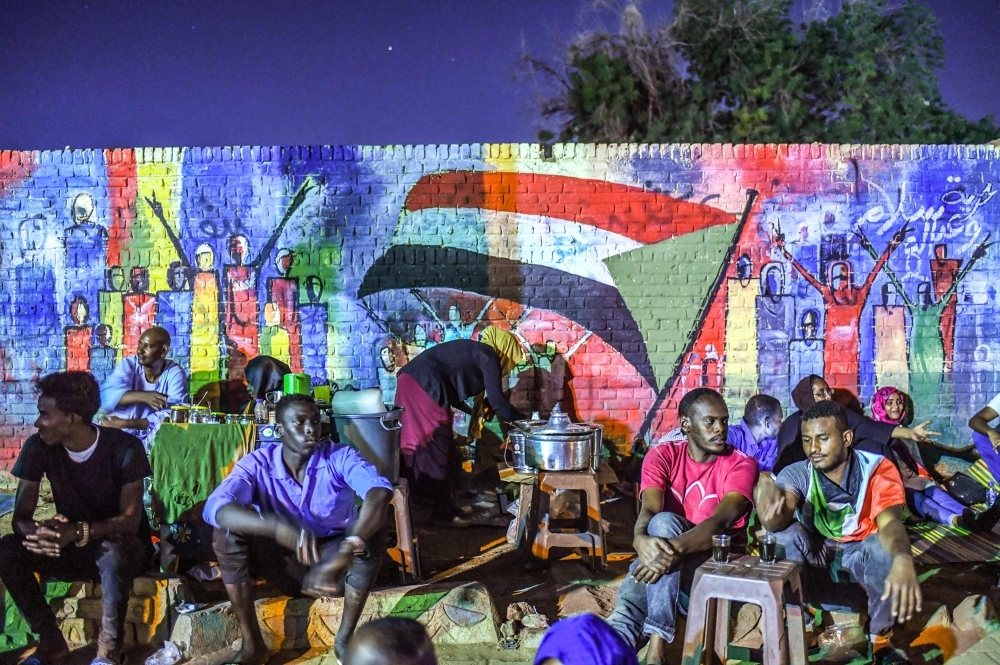 In this file photo taken on April 24, 2019, Sudanese protesters sit in front of a recently painted mural during a demonstration near the army headquarters in the capital Khartoum. -AFP